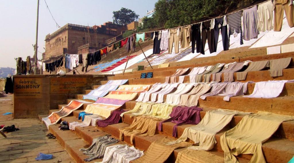 Farbenfrohe Sari Stoffe werden zum Trocknenauf den schlammigen Steintreppen ausgelegt.