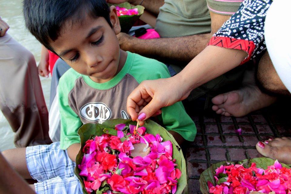 Bei der abendlichen Puja in Haridwar: Blumenboote, Opfergaben und Kerzen schmücken den Ganges.